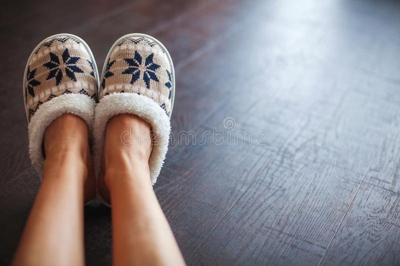 Slippers on women`s legs. Soft comfortable home slipper royalty free stock image