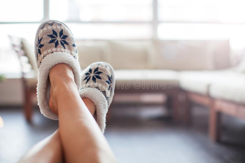 Slippers on women`s legs. Soft comfortable home slipper royalty free stock photo