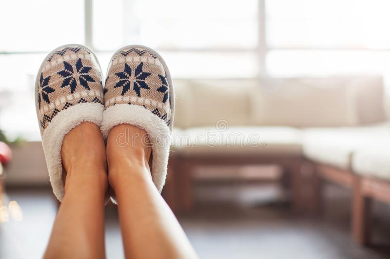 Slippers on women`s legs. Soft comfortable home slipper stock image