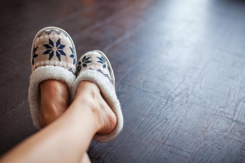 Slippers on women`s legs. Soft comfortable home slipper stock images