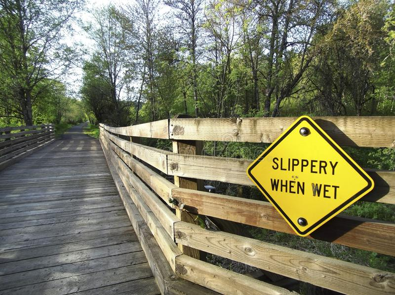 Slippery When Wet Sign and Bridge. Slippery When Wet signage and wood bridge on a rural country path. Watch your step stock photography
