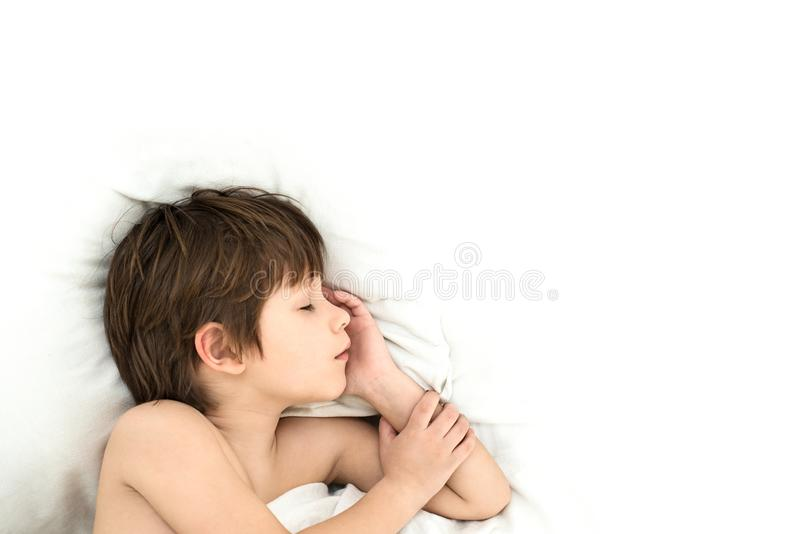 Boy lies in a bed on a white bedclothes. slipping child. Slipping boy 6 years with a lies in a bed on a white bedclothes stock photos