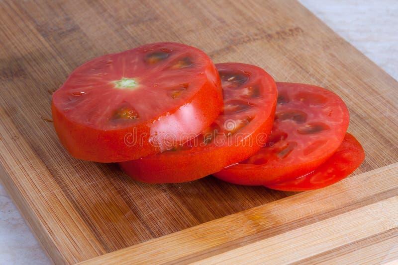 Slises свежего томата на деревянной разделочной доске стоковая фотография rf