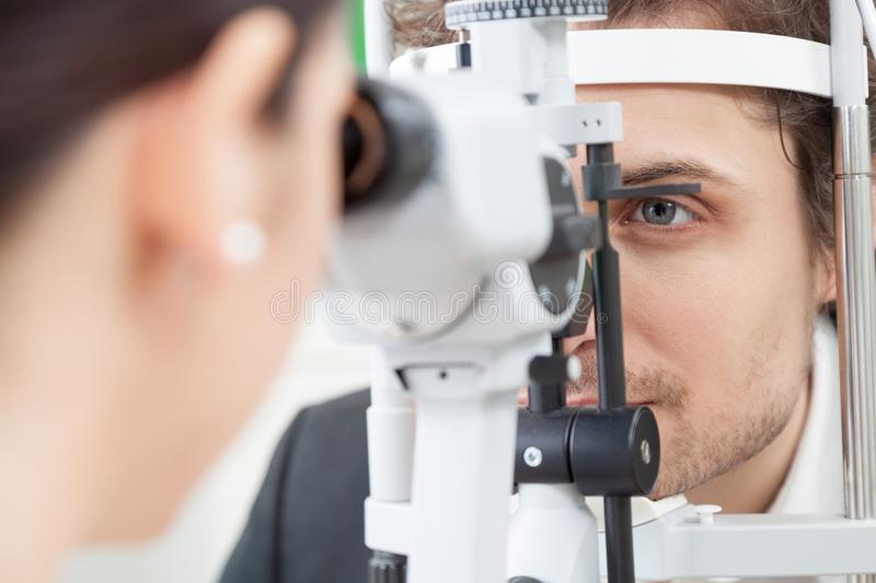 Slit Lamp eye control with the Ophthalmologist. / handsome men during a contact lenses examining / the oculist in eyes clinic doing cornea and retina exam royalty free stock photography