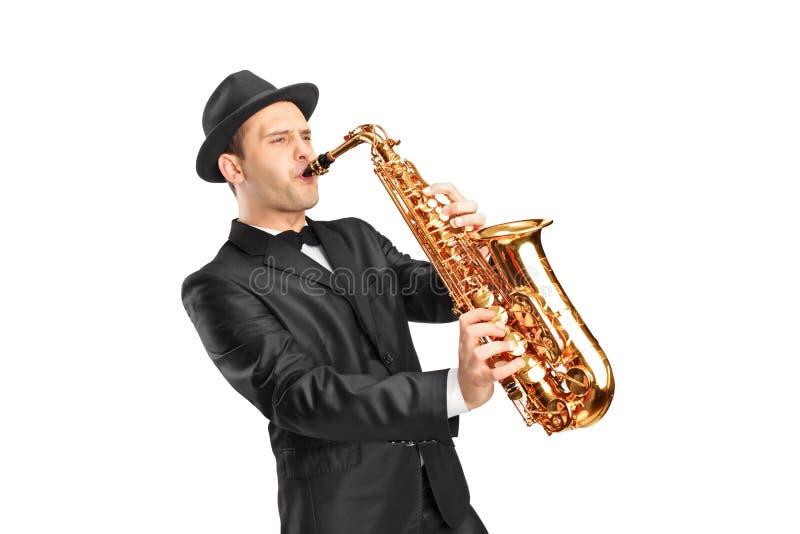 Slitage hatt för ung man och leka på saxofon arkivbilder