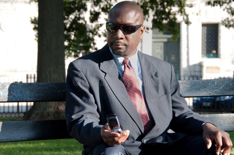 Slitage solglasögon Texting för affärsman utomhus royaltyfria bilder