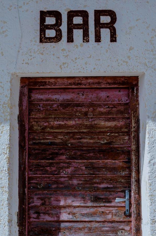 Sliten dörr av en gammal stång arkivfoton