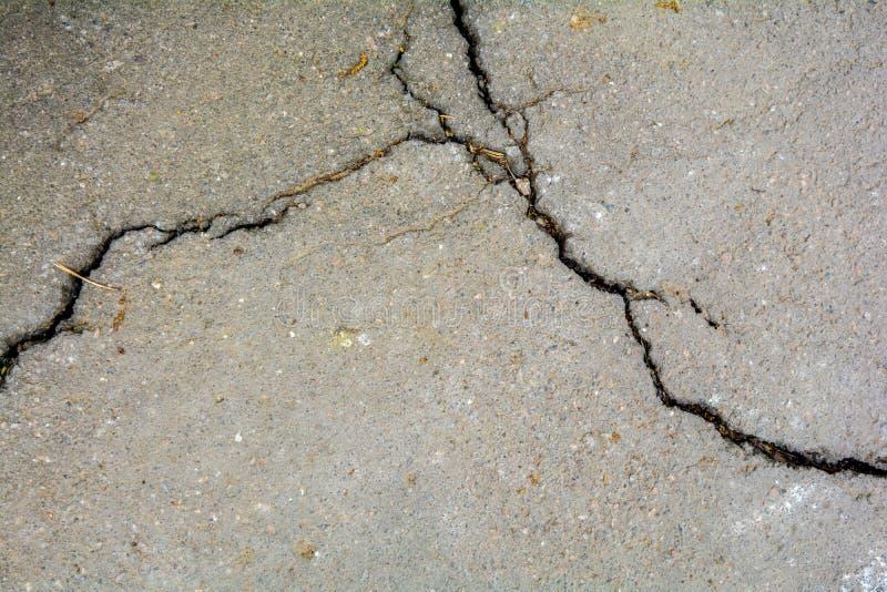 Sliten och sprucken asfalt med stora sprickor Konkret textur för gammal väg royaltyfria bilder