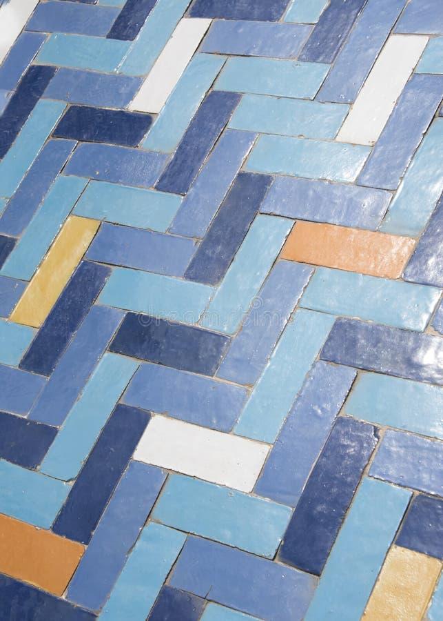 Slitet belagt med tegel golv i fiskbensmönstermodell, i blått, apelsin och vit royaltyfri foto