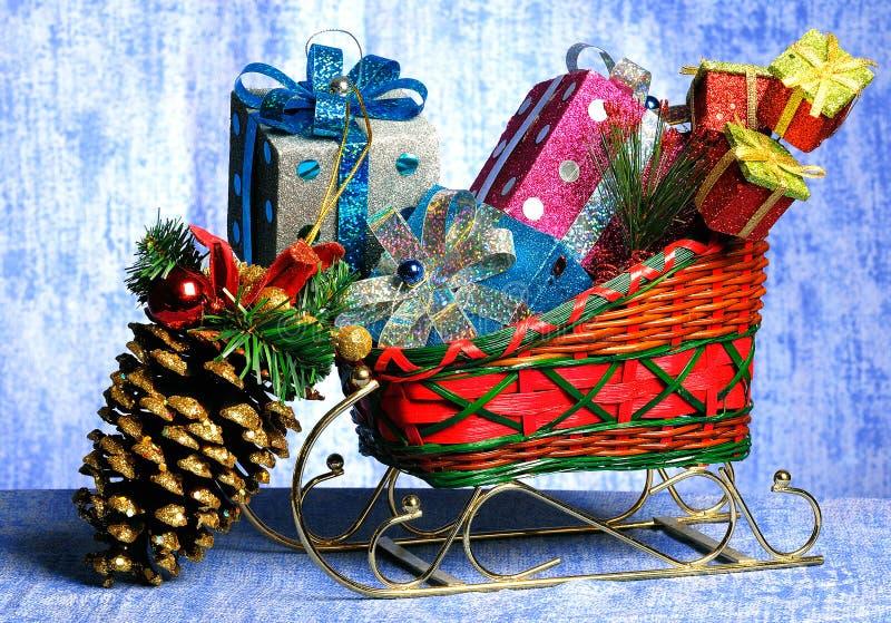 Slitta con i regali ed i giocattoli ad un pelliccia-albero di natale immagine stock libera da diritti