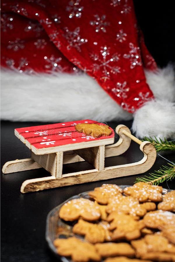 Slitta di legno del giocattolo e un cappello biscotti del pan di zenzero dei biscotti di Natale e di Santa Claus su un vassoio d' fotografia stock libera da diritti