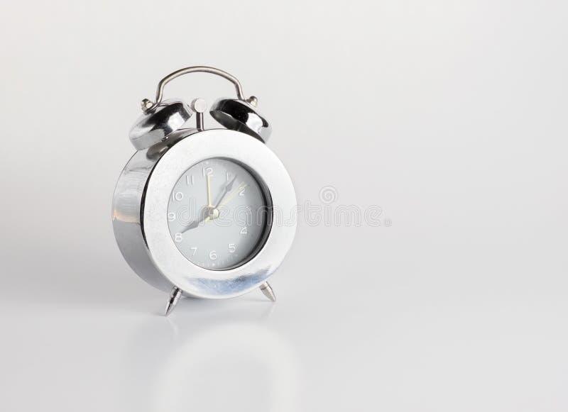 Sliver alarm clock on gery background.  royalty free stock image