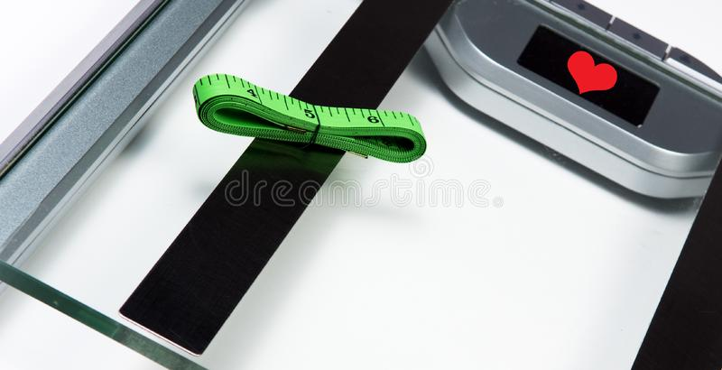 Sliver bathroom scale with green measuring tape on white background.  Health and weight loss Concept stock images