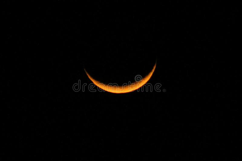 Yellow crescent moon in a starless sky. Sliver of a crescent moon surrounded by the dark abyss of night as seen from earth royalty free stock images