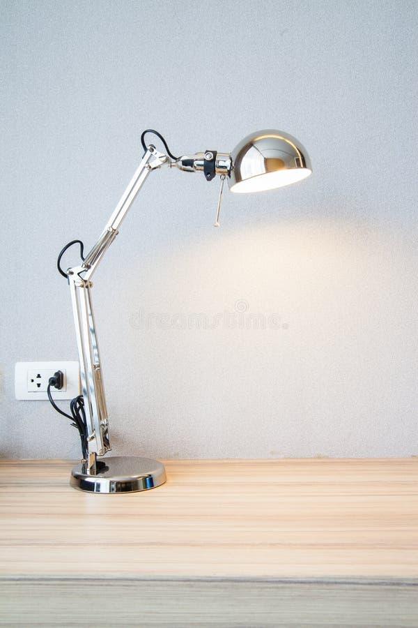 Sliver desk lamp on wood desk. Swithc on sliver desk lamp on wood desk royalty free stock photo