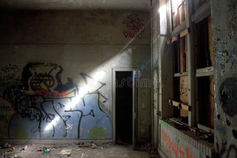 Sliver of Light. Light breaks through the boarded up windows of the Annie Lytle School Jacksonville, FL illuminating the debris and graffiti left there by stock images