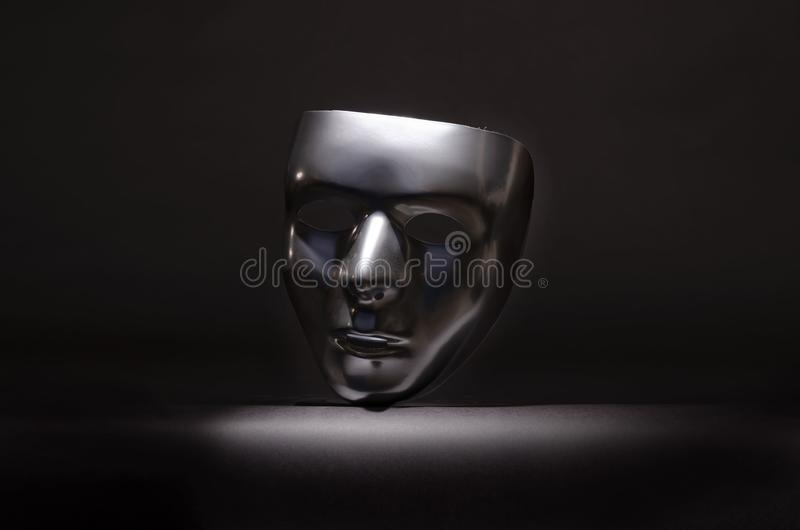 Sliver masquerade mask in shadow. A shiny silver blank masquerade mask in shadow against a black background with blue highlights creates a moody environment royalty free stock images