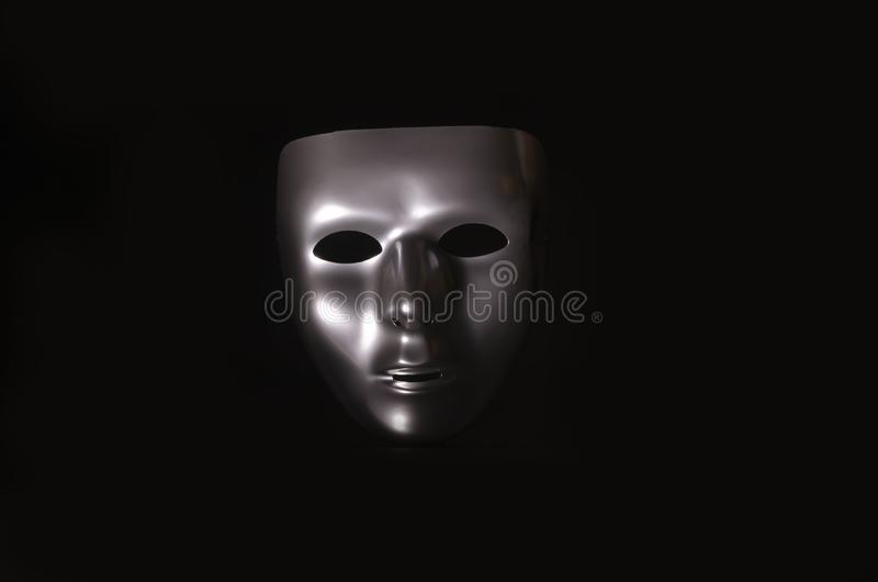 Sliver masquerade mask in shadow. A shiny silver blank masquerade mask in shadow against a black background with blue highlights creates a moody environment stock photography