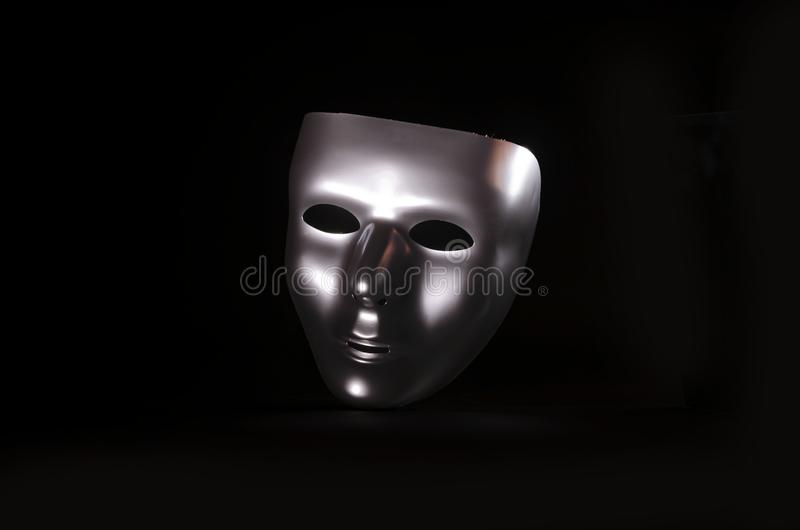 Sliver masquerade mask in shadow. A shiny silver blank masquerade mask in shadow against a black background with blue highlights creates a moody environment stock image