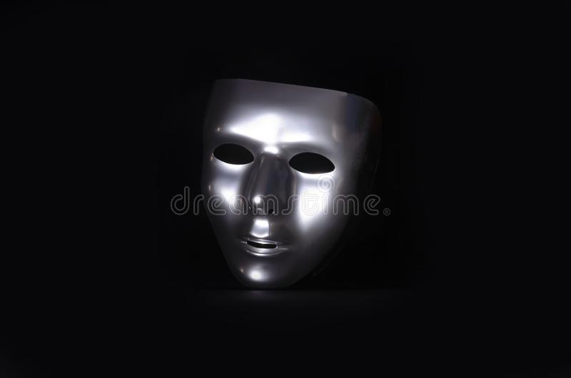Sliver masquerade mask in shadow. A shiny silver blank masquerade mask in shadow against a black background with blue highlights creates a moody environment royalty free stock image
