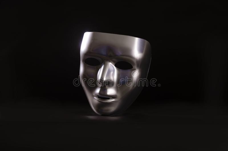 Sliver masquerade mask in shadow. A shiny silver blank masquerade mask in shadow against a black background with blue highlights creates a moody environment royalty free stock photos