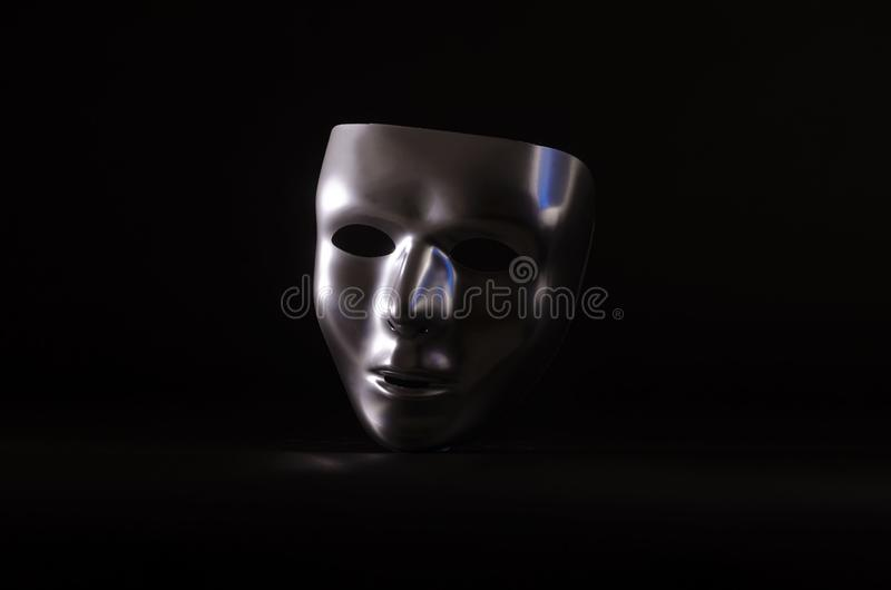 Sliver masquerade mask in shadow. A shiny silver blank masquerade mask in shadow against a black background with blue highlights creates a moody environment royalty free stock photo