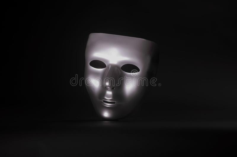 Sliver masquerade mask in shadow. A shiny silver blank masquerade mask in shadow against a black background with blue highlights creates a moody environment stock images