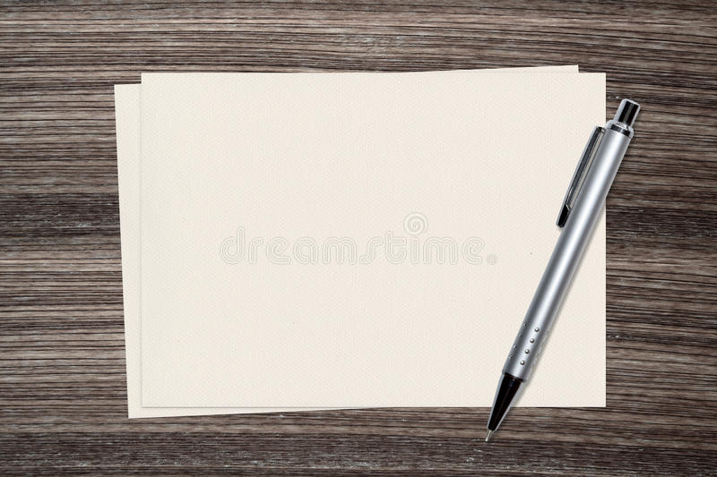 Sliver Pen and paper on wood background stock photography