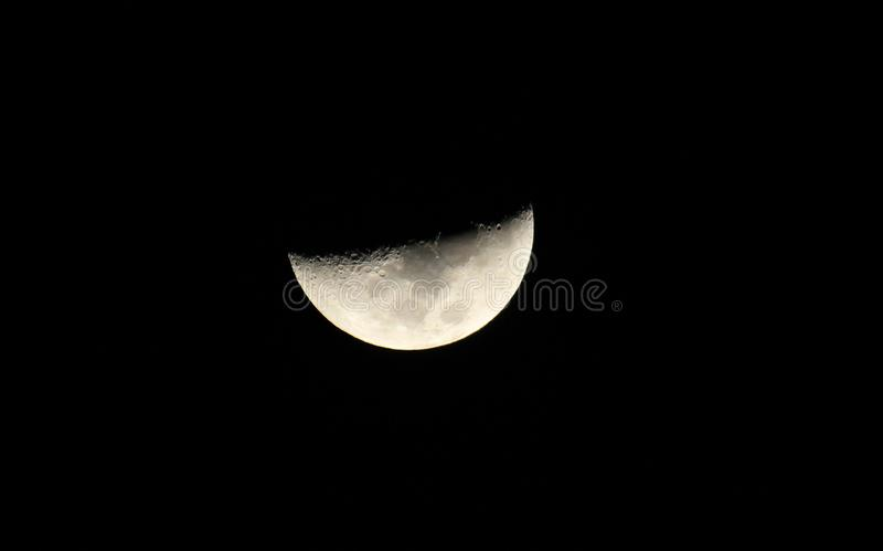 Silver half moon in a starless sky. Sliver of a silver crescent moon surrounded by the dark abyss of night as seen from earth stock image