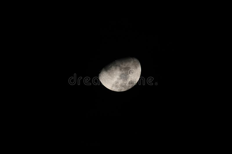 Silver waxing gibbon moon in a starless sky zoomed. Sliver of a silver waxing gibbon moon surrounded by the dark abyss of night as seen from earth closeup stock photo