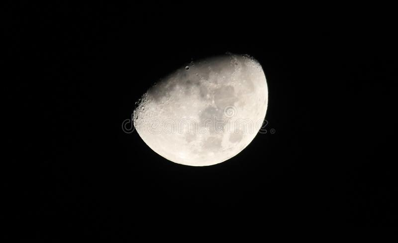 Silver waxing gibbon moon in a starless sky. Sliver of a silver waxing gibbon moon surrounded by the dark abyss of night as seen from earth stock image