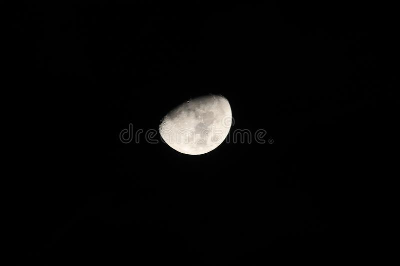 Silver waxing gibbon moon in a starless sky. Sliver of a silver waxing gibbon moon surrounded by the dark abyss of night as seen from earth royalty free stock image