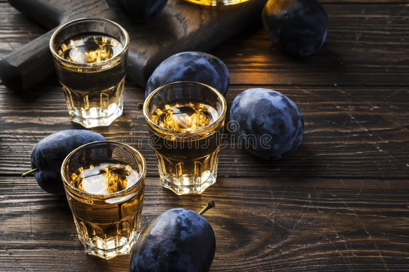 Slivovica - plum brandy or plum vodka, hard liquor, strong drink in glasses on old wooden table, fresh plums, copy space royalty free stock photo