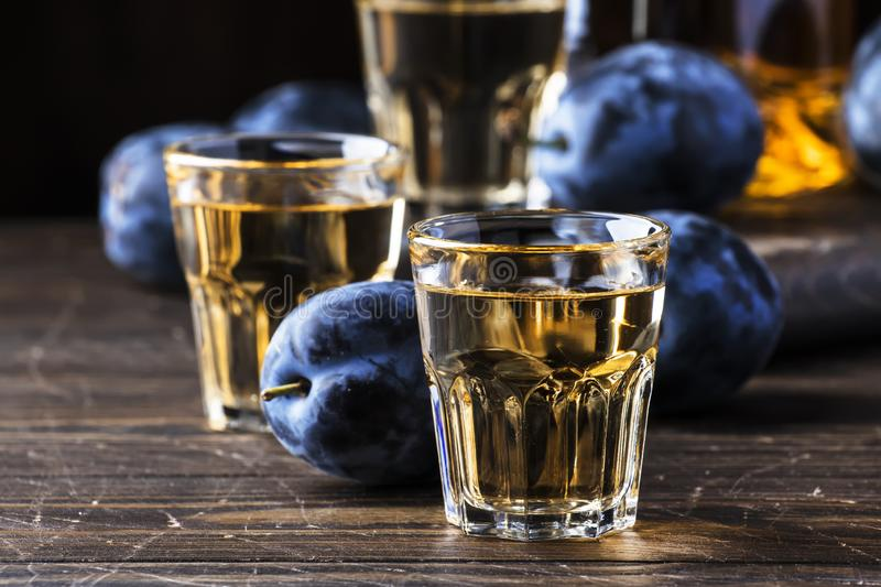 Slivovica - plum brandy or plum vodka, hard liquor, strong drink in glasses on old wooden table, fresh plums, copy space stock photo