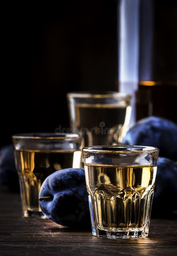 Slivovica - plum brandy or plum vodka, hard liquor, strong drink in glasses on old wooden table, fresh plums, copy space. Slivovica - plum brandy or plum vodka royalty free stock image