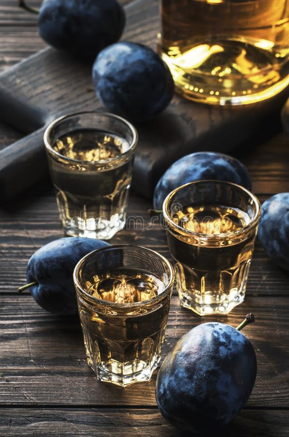 Slivovica - plum brandy or plum vodka, hard liquor, strong drink in glasses on old wooden table, fresh plums, copy space stock images