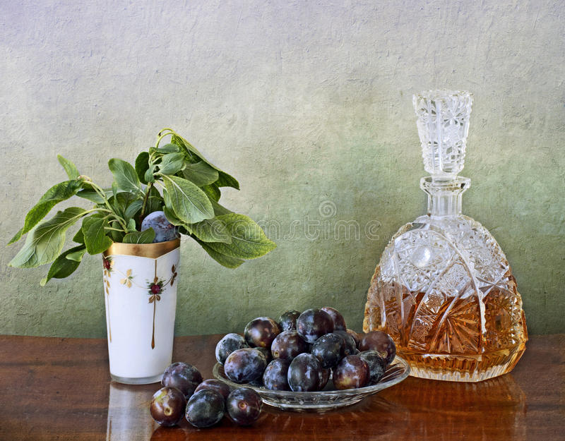 Slivovitz crystal bottle and plums. Slivovitz is a Balkan liqueur distilled by ripe or overripe plums, its color ranges from rich tawny to transparent white.The royalty free stock photography