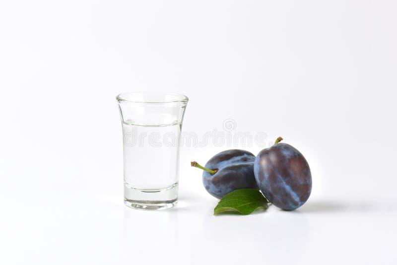 Slivovitz and plums. Slivovitz (plum brandy) and fresh plum on white background stock photos