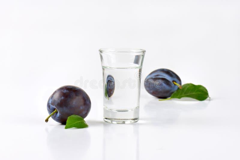 Slivovitz and plums. Slivovitz (plum brandy) and fresh plums on white background stock photo