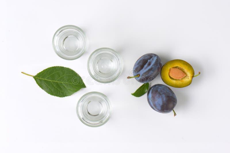 Slivovitz and plums. Slivovitz (plum brandy) and fresh plums on white background royalty free stock photo