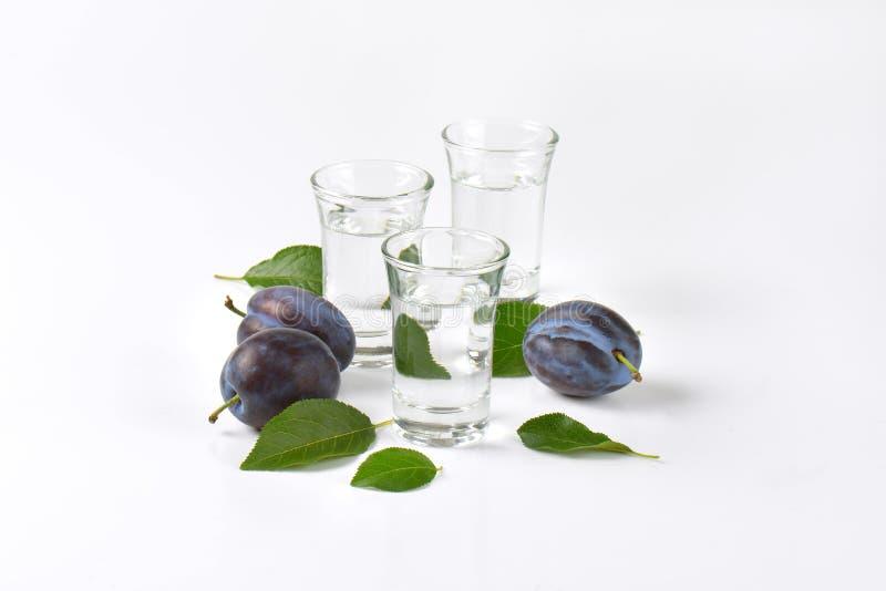 Slivovitz and plums. Slivovitz (plum brandy) and fresh plums on white background stock photography