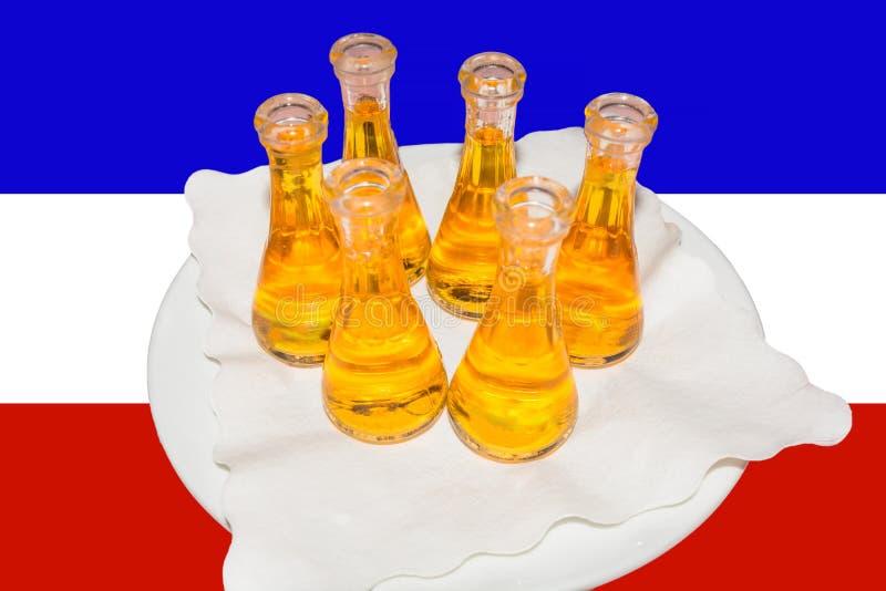 Slivovitz on a white plate. Plum brandy also called slivovitz on a white plate in the background, the flag of Yugoslavia stock image
