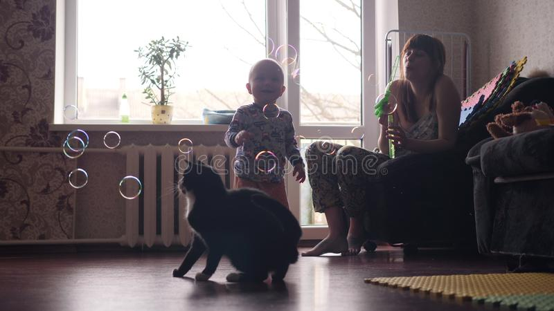A young beautiful woman blowing soap bubbles inside the room with big window on background and a little baby boy and a stock photo