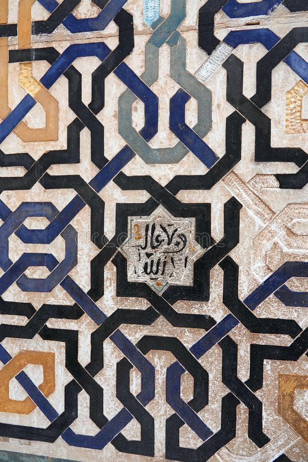 Geomatrical lined wall of Nasrid palace of the Alhambra in Granada, Andalusia. Slogan of the Nasrid kingdom of Granada: Only Allah is victorious at the Court of royalty free stock photos