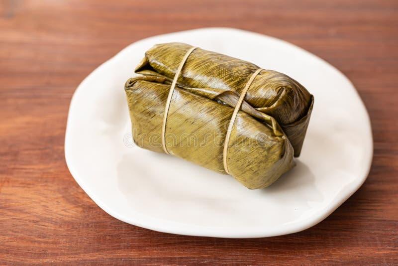 Slogg in klibbiga ris för thailändsk efterrätt, den slågna in bananen i söta klibbiga ris som burritostil och därefter dem inom b arkivfoton