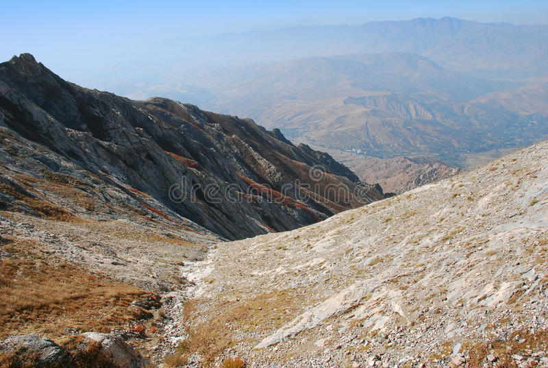 Slope with footpath on the background of the panorama of mountains of Tien Shan royalty free stock photo
