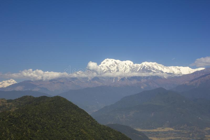 The slope of a green hill on the background of the Annapurna mountain range with snowy peaks with clouds under a clear blue sky. royalty free stock images