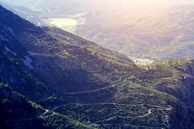 Slope of the mountain near the Lassithi plateau with views of the lake and the village , the setting sun, the evening. Crete. Sun valley of Greece. Beautiful royalty free stock photography