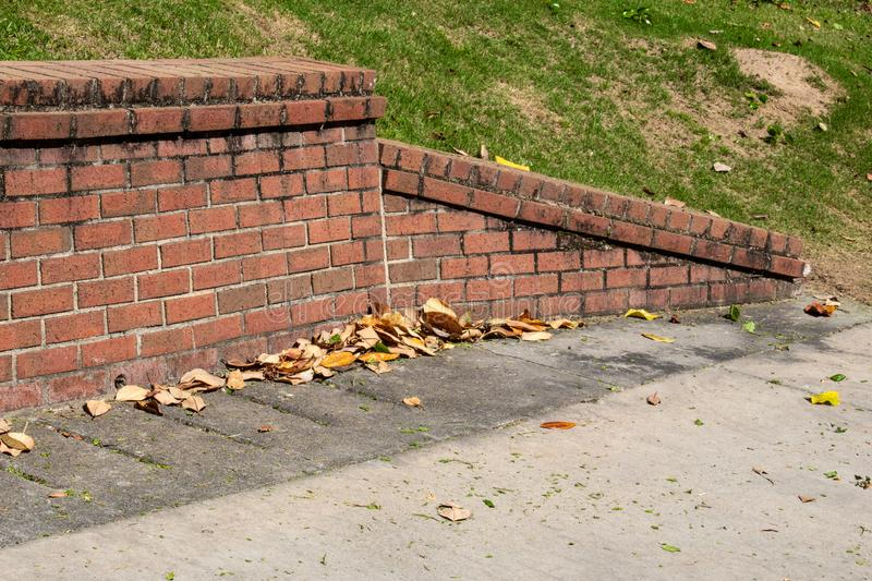 Sloped end piece of old brick retaining wall, concrete with magnolia leaves royalty free stock images