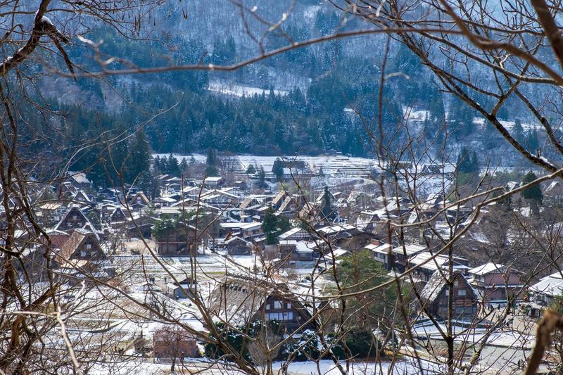 The sloped-roof and thatched-roof houses of snow cover and started to melt with a view of the branches in the foreground. At Shirakawa-go, Japan stock photo